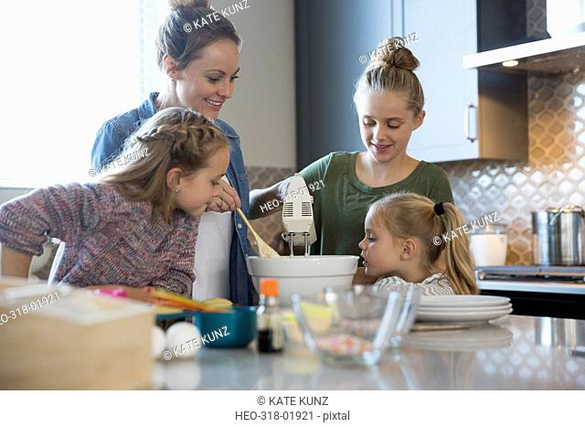 Mother and daughters baking in kitchen using hand mixer