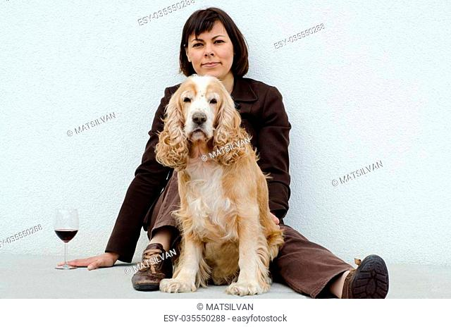 Relaxed woman sitting down with her dog and a glass of red wine