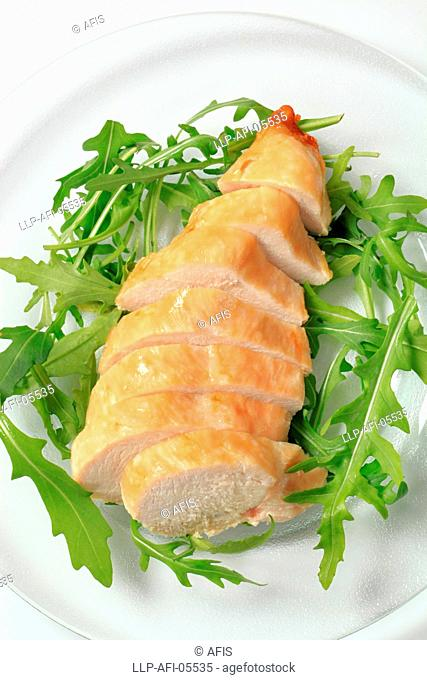 Sliced chicken breast fillet on a nest of salad greens