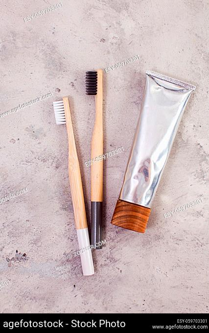 Bamboo teeth brushes and tube of toothpaste on minimalistic concrete backgroud, top view, flat lay. Zero waste concept