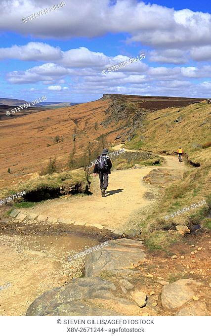 Walker and cyclist heading down Long Causeway off Stanage Edge near Hathersage, Peak District National Park, Derbyshire, England, UK