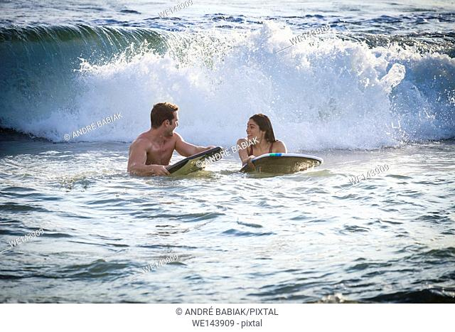 Young woman and man waiting for wave to ride out on boogie board