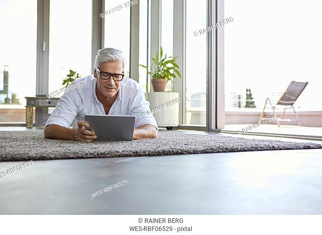 Mature man lying on carpet at home using tablet