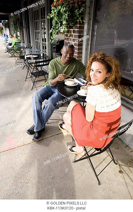 Portrait of smiling a young couple sitting at a table at a sidewalk cafi