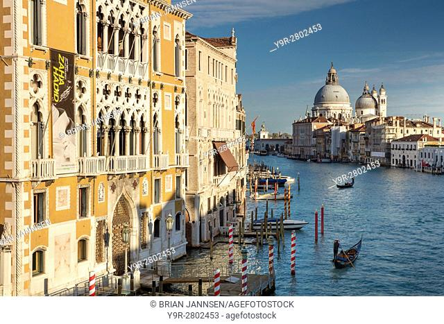 Buildings and boats along the Grand Canal with the domes of Santa Maria della Salute beyond, Venice, Veneto, Italy