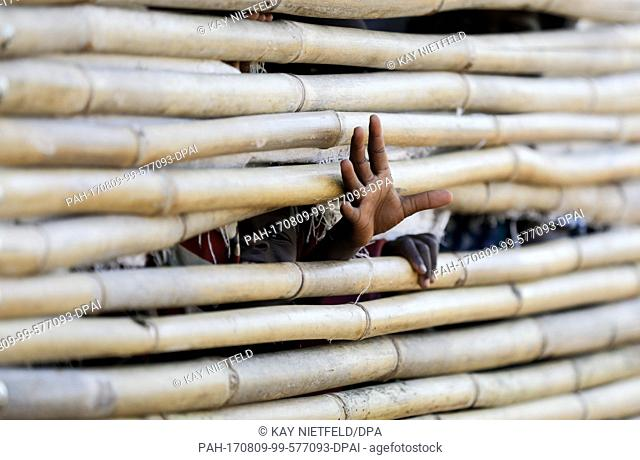 A child's hand stretches through a hole in a fence in the Rhino Camp, a refugee camp for displaced children from South Sudan, in Ofua, Uganda, 9 August 2017