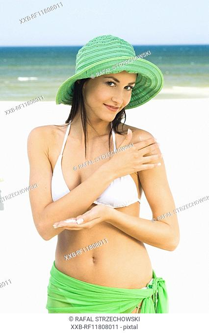 woman creaming shoulders on beach