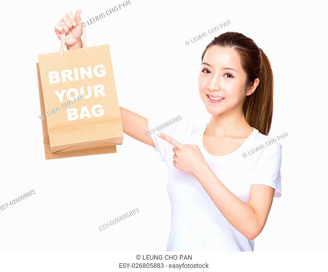Woman finger point to shopping bag and showing phrase of bring your bag