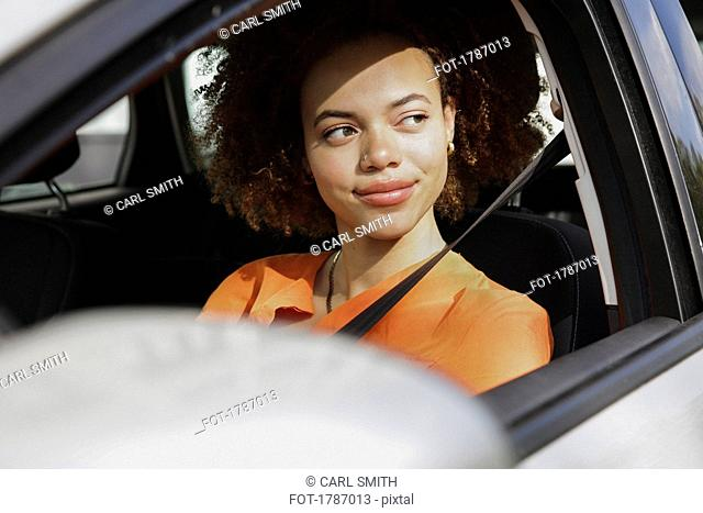 Confident young woman driving car