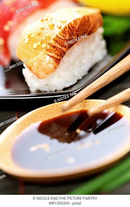 set of japanese sushi with chopsticks and soy sause over white