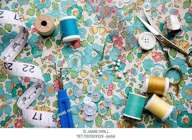 Spools of thread, seam ripper, and measuring tape