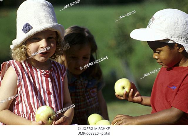 Three little children, a boy and two girls, 1-5 years old, in the garden in summer