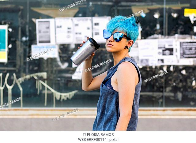 Portrait of young woman with dyed blue hair wearing mirrored sunglasses