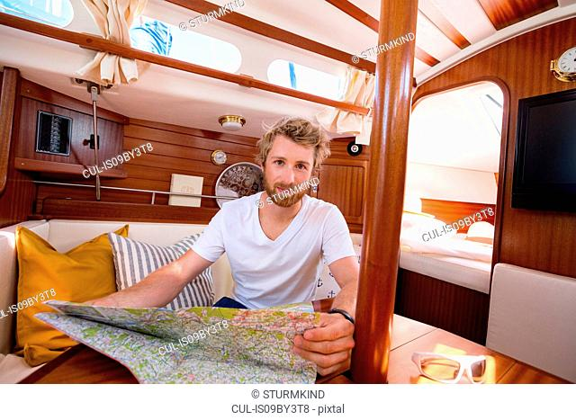 Young man in sailboat cabin with folding map, portrait