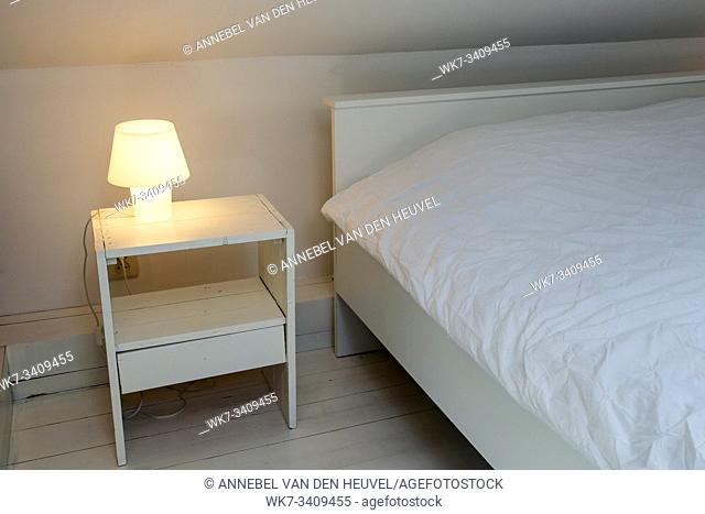 Night light lamp next to bed in the bedroom, white wooden floor and bed, modern design clean