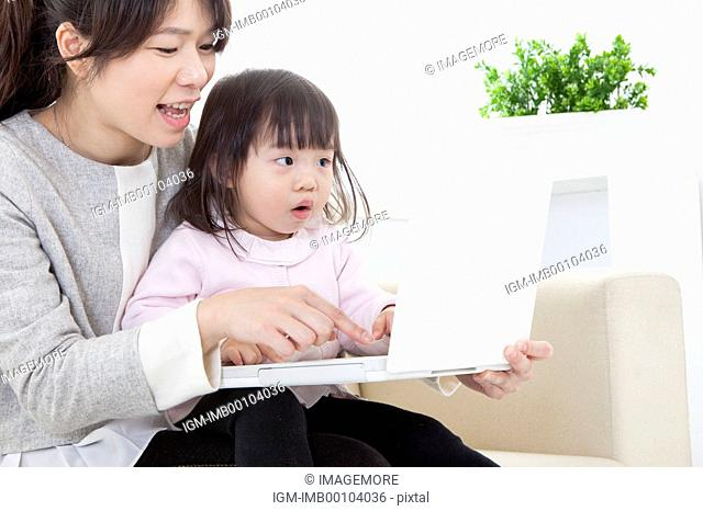 Mother and baby girl playing laptop together