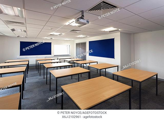 Empty new school classroom laid out with desk tables