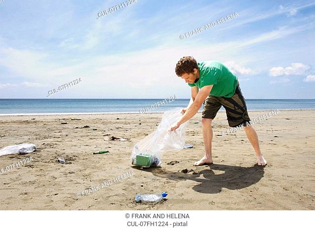 Young man collecting garbage on beach