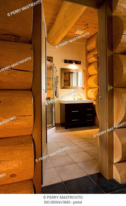 Guest bathroom with glass shower stall and wooden vanity inside a Scandinavian cottage style log home