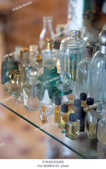 Vintage scent bottles on display shelf in handmade soap workshop
