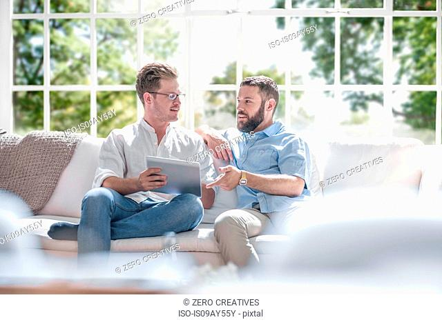 Men chatting and using digital tablet on sofa