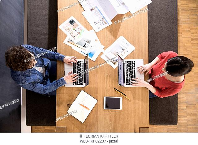 Overhead view of man and woman using laptops on table