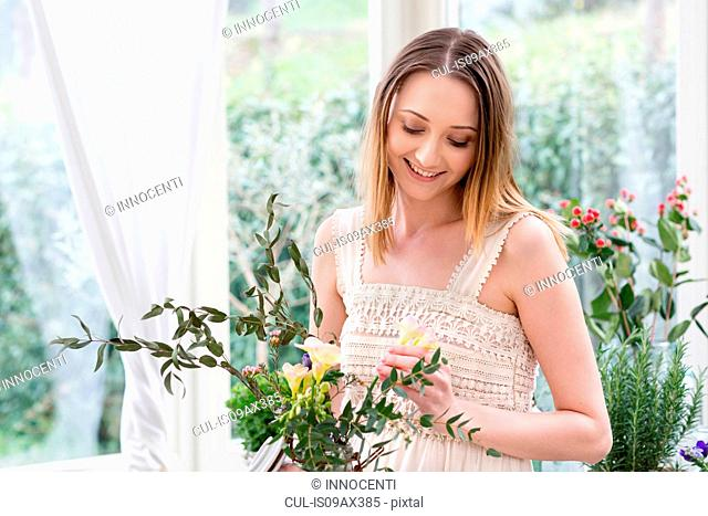 Woman arranging flowers looking down smiling