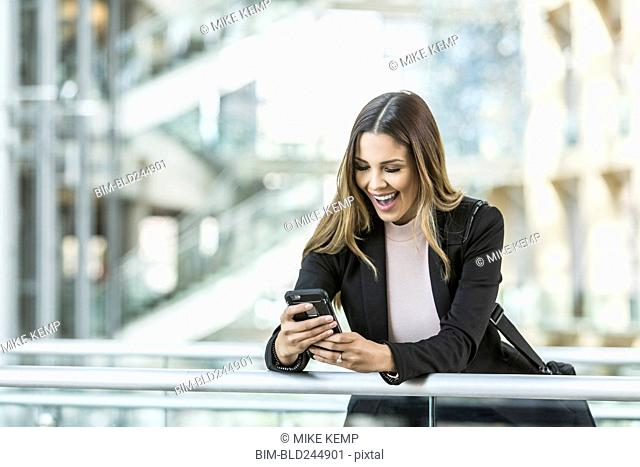 Mixed Race businesswoman texting on cell phone leaning on railing in lobby