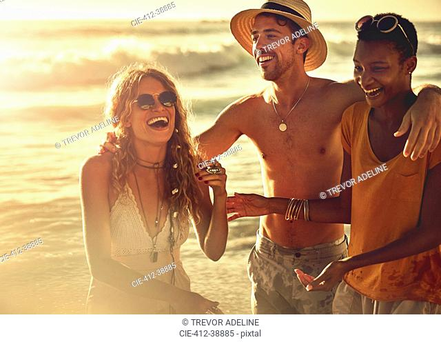 Laughing young friends on sunny summer beach