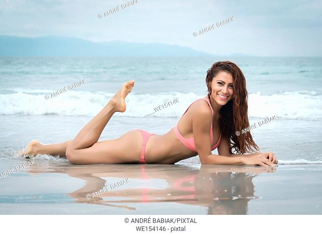 Attractive woman in bikini lying in the sand close to water at a beach