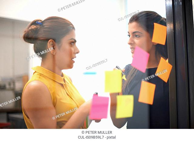 Two businesswomen behind sticky notes on office glass wall having discussion