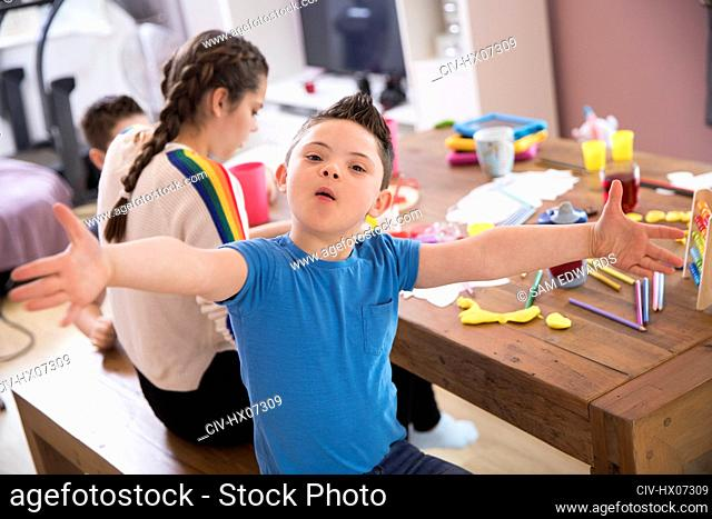 Portrait playful boy with Down Syndrome playing at dining table
