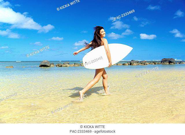 A young woman in a strapless bikini with a surfboard; Kauai, Hawaii, United States of America
