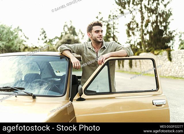 Smiling young man leaning on car door