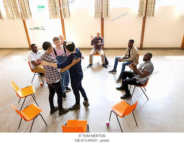 Men hugging and clapping in group therapy