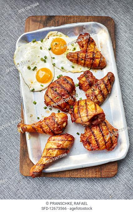 Marinated, grilled chicken bits with fried eggs