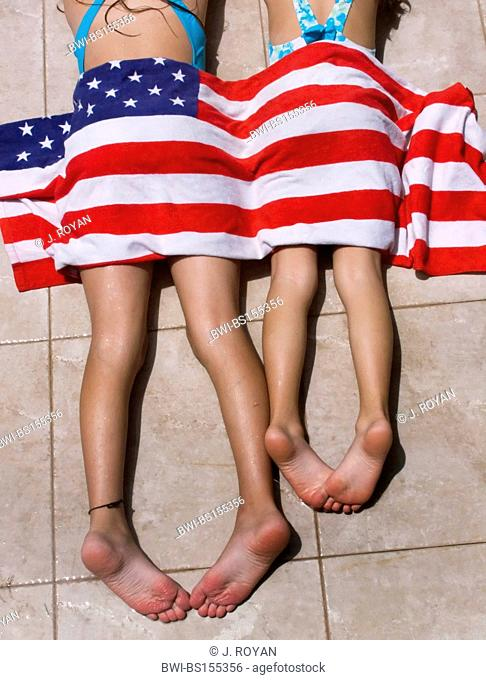 two girls lying in the sun with an american flag towel covering them, USA