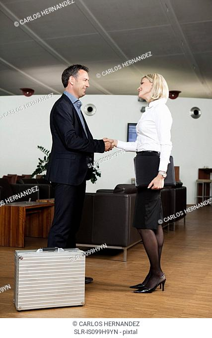 Business partners shaking hands in airport
