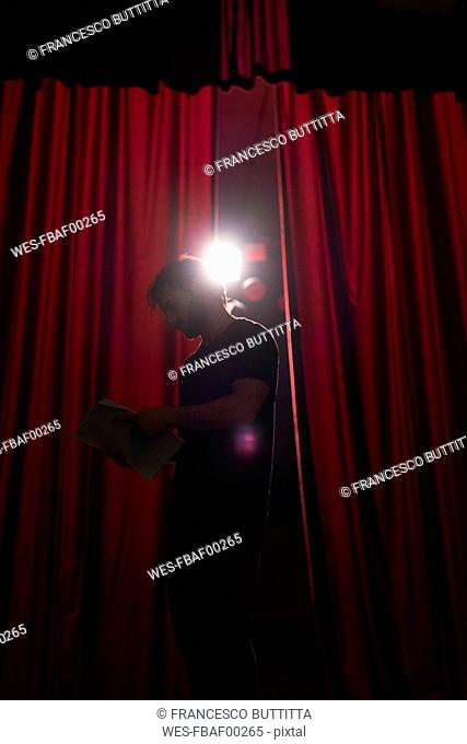 Actor standing on stage of theatre studying script