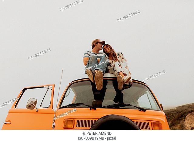 Young couple sitting on top of recreational vehicle, Jalama, California, USA