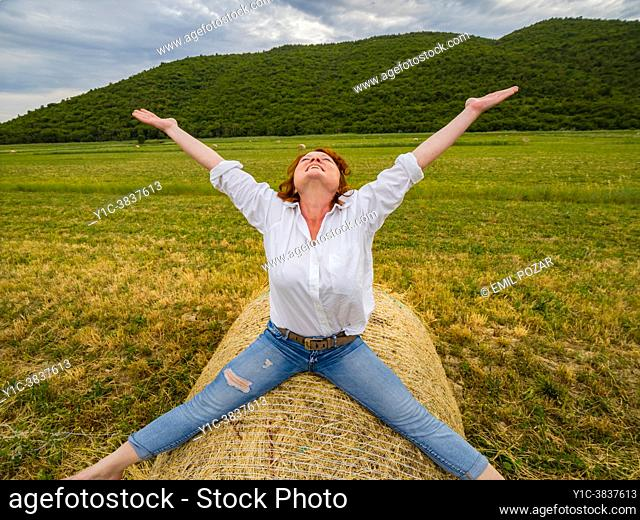 Joy of life mature woman spreading wide on countryside haystack looking up joy of life