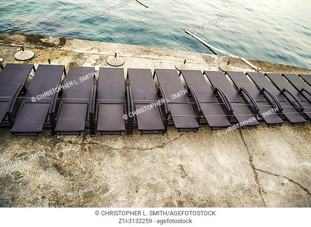 Empty beach chairs lined up like black paino keys on the waterfront at sundown in Opatija on the Adriatic sea in Croatia