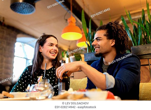 leisure, eating, food and drinks, people and holidays concept - happy couple with drinks at cafe or bar