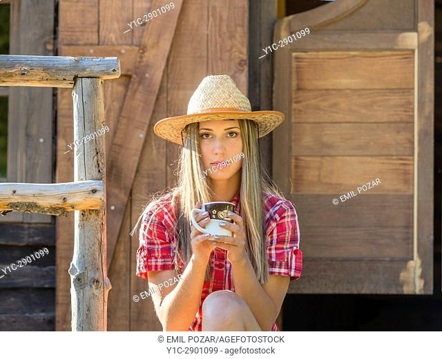 Country-girl with cup of coffee in hand facing camera
