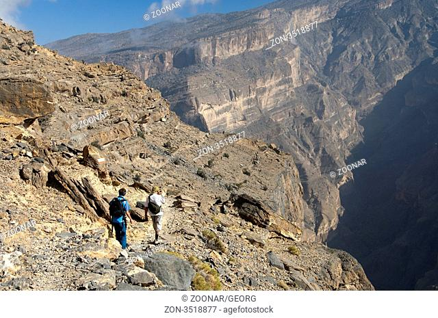 Wanderer im Grand Canyon von Oman im Wadi Nakhur am Fuss des Jebel Shams Gipfels, Al Hajar Gebirge, Sultanat Oman / Hikers in the Grand Canyon of Oman in Wadi...
