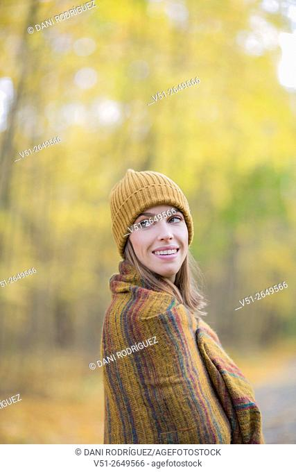 Brunette Woman in Park in Autumnn covering with a blanket