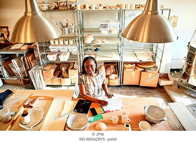 Woman at desk in pottery studio with paperwork