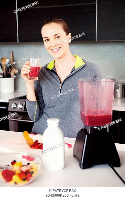 Woman with a glass of freshly made smoothie