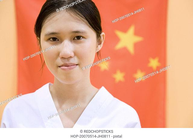 Portrait of a young woman with a Chinese flag in the background