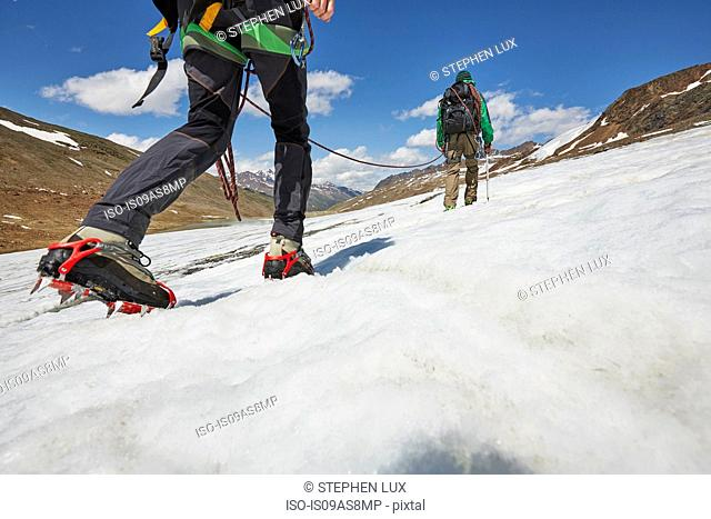 Young couple hiking up ice on Val Senales Glacier, Val Senales, South Tyrol, Italy